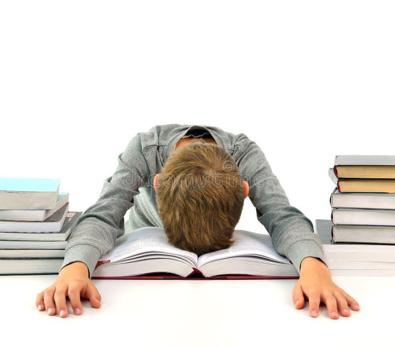 Müder und gebohrter Junge mit Büchern stockfotografie