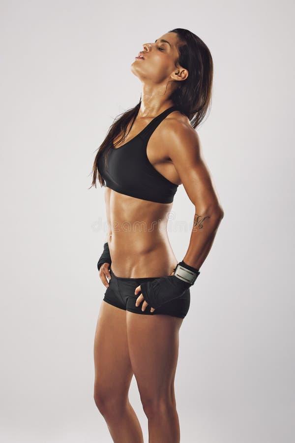 Müder weiblicher Boxer, der nach einem Training sich entspannt stockfotografie