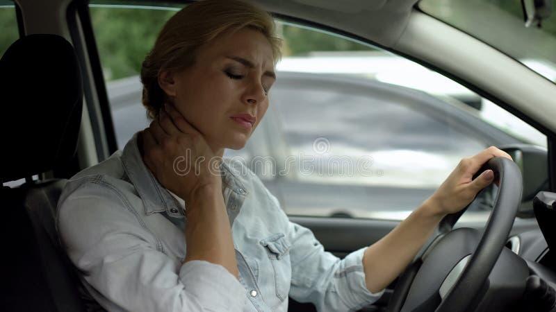 Müder weiblicher Fahrer, der im Selbst- und massierenden Hals nach langer Autoreise sitzt stockfoto