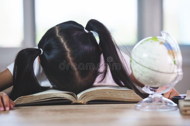 Müdes asiatisches Kindermädchen, das über dem geöffneten Buch im Klassenzimmer schläft lizenzfreies stockfoto