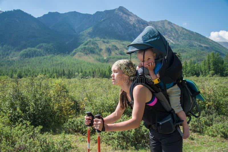 Müdes Frauen-Wanderertrekking in den Bergen mit Kind im Rucksack, gestoppt für Rest Mutter mit dem Baby, das herein reist stockbilder