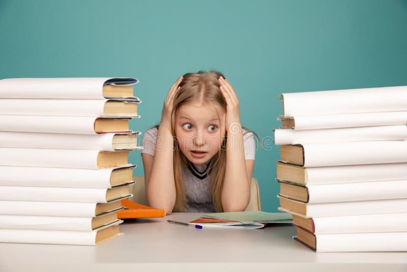Müdes jugendlich Mädchen mit Büchern auf dem Hintergrund einer Schulbehörde, die Kamera betrachtet Raum f?r Text lizenzfreie stockfotografie