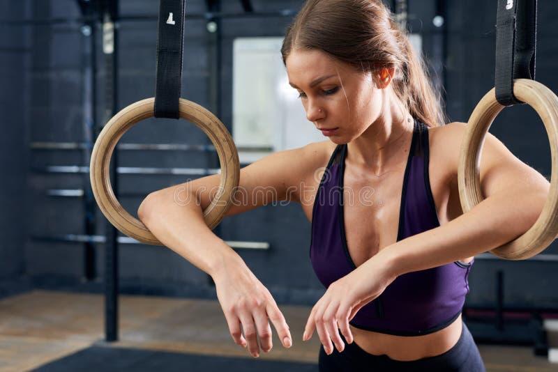 Müdes junge Frauen-Training auf gymnastischen Ringen stockbilder