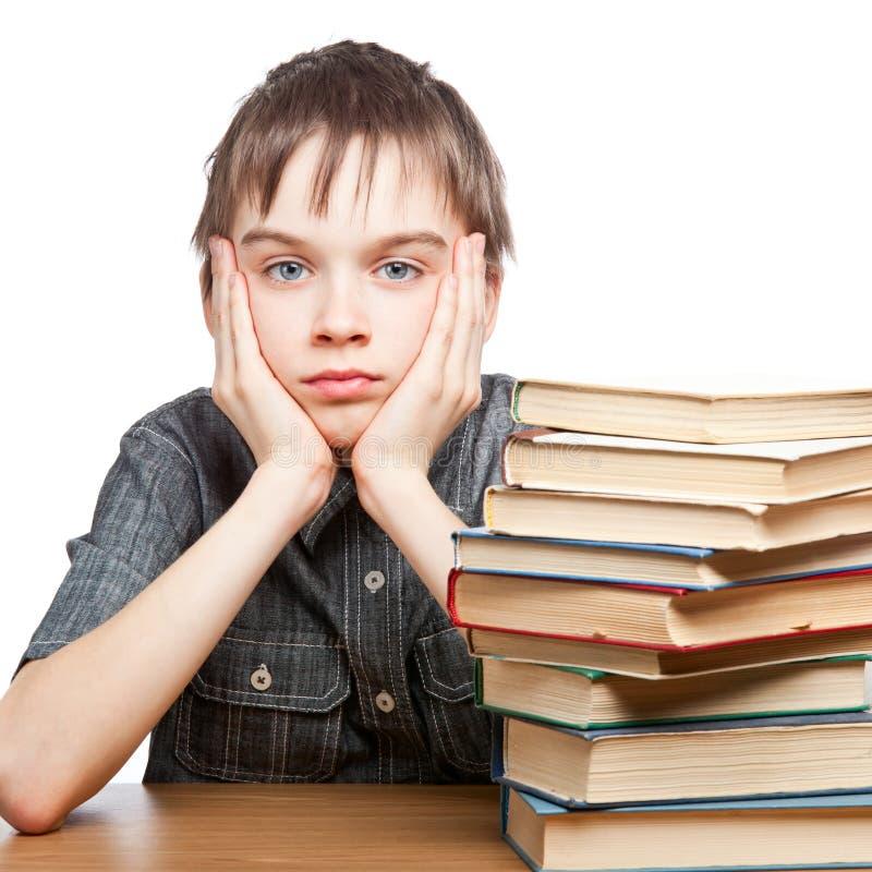 Müdes Kind mit Stapel Büchern lizenzfreie stockfotos