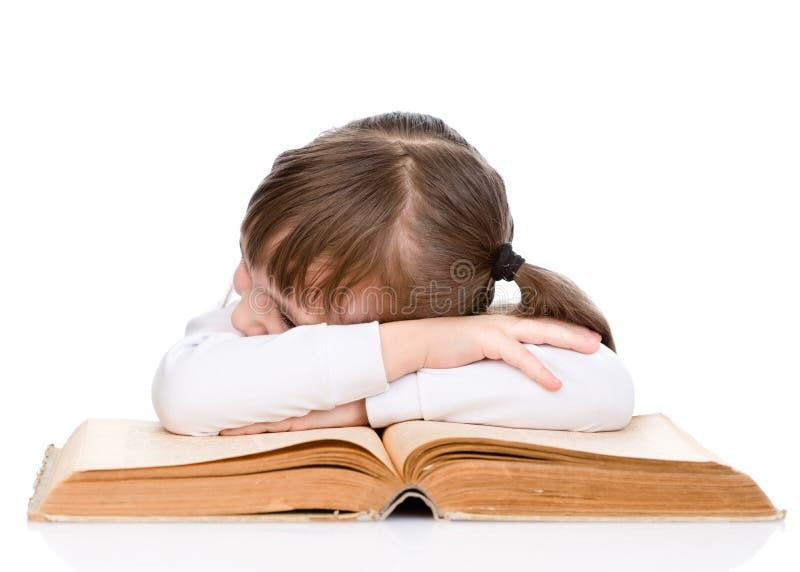 Müdes kleines Mädchen, das auf dem Buch schläft Lokalisiert auf Weiß lizenzfreie stockfotos