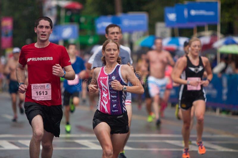 Müdes Läufer-Drängung auf Ziellinie an Peachtree-Straßenrennen stockfoto