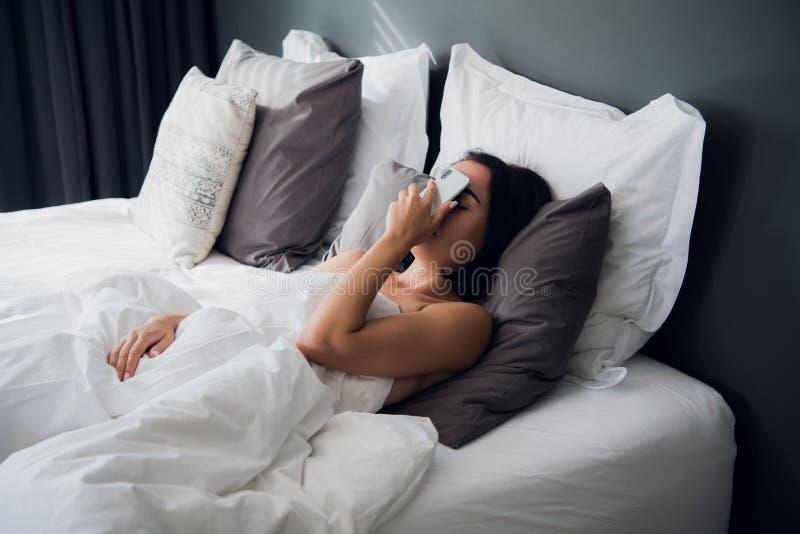 Müdes Mädchen, das in einem Bett schläft Schlafen Sie mit dem Handy auf ihrem Gesicht ein Facepalm-Geste mit einem Telefon lizenzfreie stockbilder