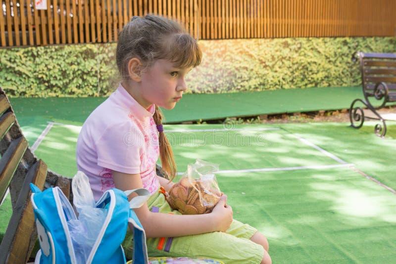 Müdes Mädchen im Park sitzt auf einer Bank mit einem Satz Plätzchen in ihren Händen stockfoto