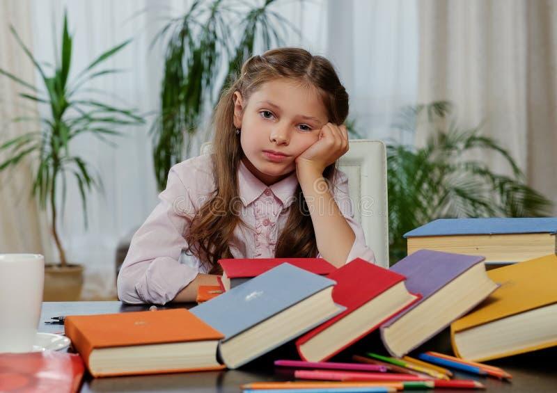 Müdes Mädchen nach dem Ablesen vieler Bücher stockfotografie