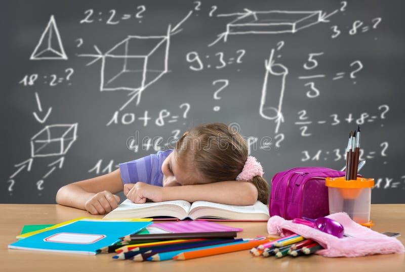 Müdes Schulmädchen, das auf der Bank, hinter harten Beanspruchungen auf dem Brett schläft lizenzfreie stockfotografie