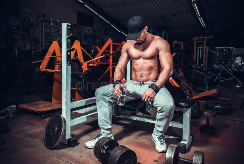 Müdes Sitzen des Muskels geformter Mann entspannt lizenzfreie stockfotos
