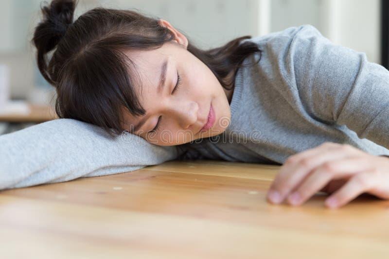 müdes Studentenmädchen, das auf dem Tisch schläft stark studieren, educati lizenzfreie stockfotos