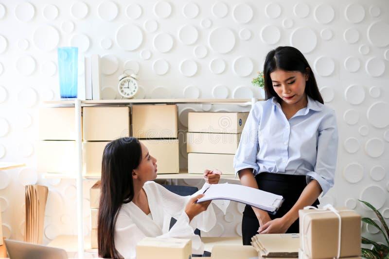 Müdes unglückliches des jungen asiatischen Mädchens ist Freiberufler Startung Kleinunternehmerschreibensadresse auf Pappschachtel stockfotografie