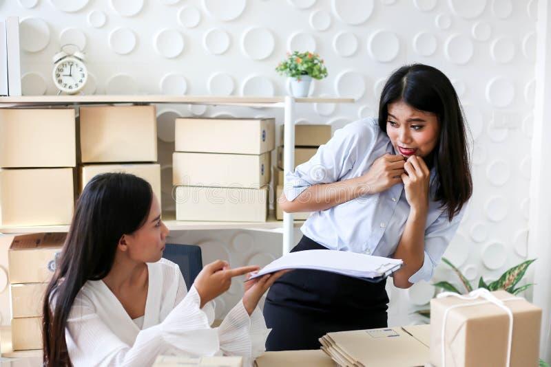 Müdes unglückliches des jungen asiatischen Mädchens ist Freiberufler Startung Kleinunternehmerschreibensadresse auf Pappschachtel stockfotos