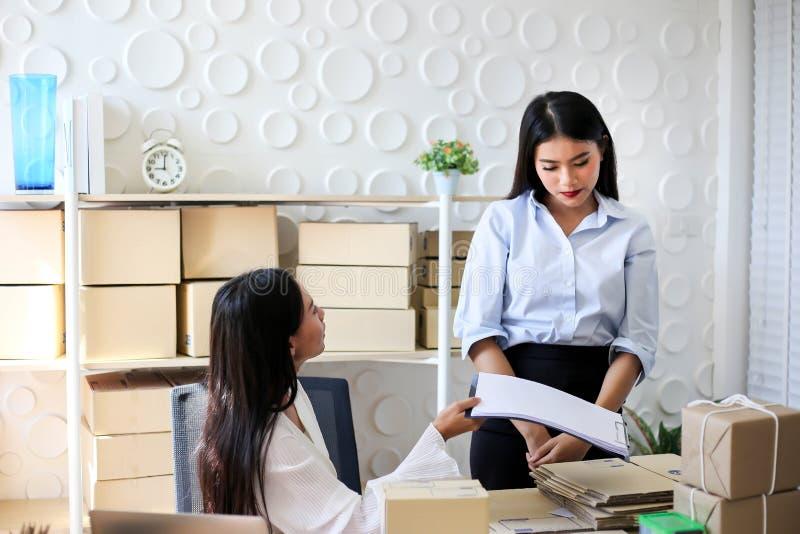 Müdes unglückliches des jungen asiatischen Mädchens ist Freiberufler Startung Kleinunternehmerschreibensadresse auf Pappschachtel stockfoto