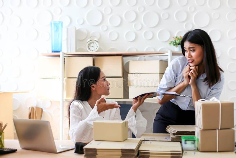 Müdes unglückliches des jungen asiatischen Mädchens ist Freiberufler Startung Kleinunternehmerschreibensadresse auf Pappschachtel stockbilder