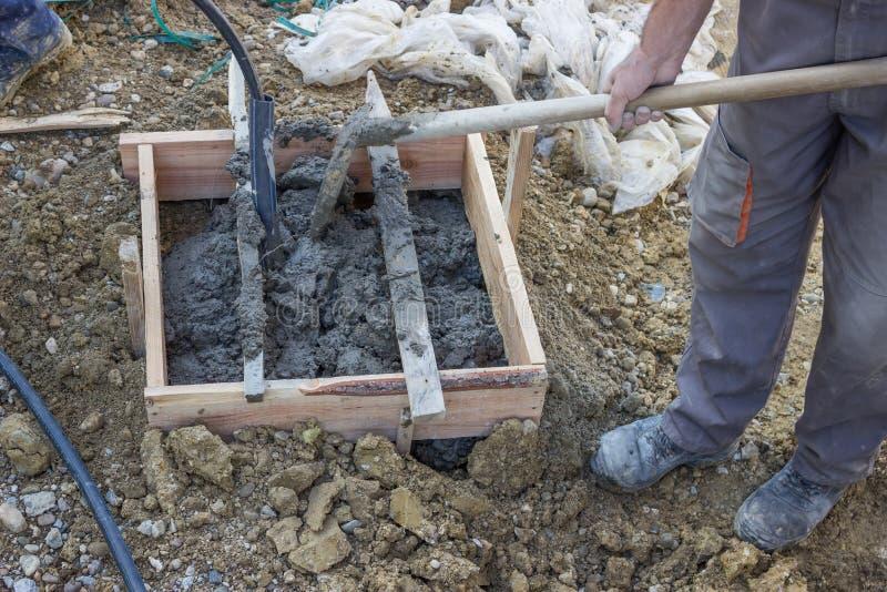 Mühsam schaufelnd, Bauarbeiter, die Beton/ceme bewegen lizenzfreie stockfotografie