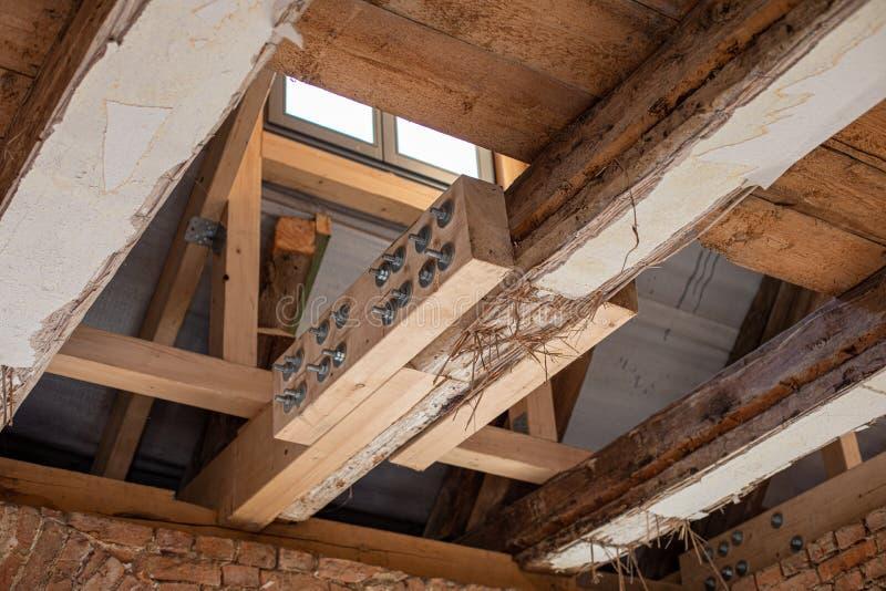 mühsame Arbeit ein altes Haus restauriert wird, wobei alte Balken durch neue verstärkt werden stockbild