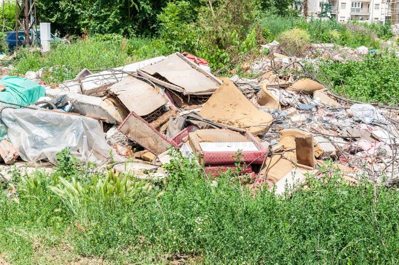 Müllkippe auf dem Gras nahe der Waldumweltkatastrophekonzept-Verschmutzungsnatur und Stadt parken mit Sänfte und Kram lizenzfreie stockbilder