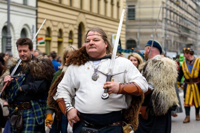 MÜNCHEN, BEIEREN, DUITSLAND - MAART 13, 2016: Groep mensen met zwaard in traditionele Schotse kleren bij St Patrick ` s Dag Parad royalty-vrije stock afbeelding