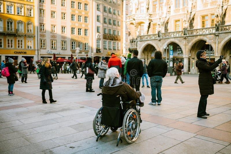 München, Deutschland, am 29. Dezember 2016: Eine ältere Frau in einem Rollstuhl überprüft den Anblick von München auf dem Hauptpl lizenzfreies stockfoto