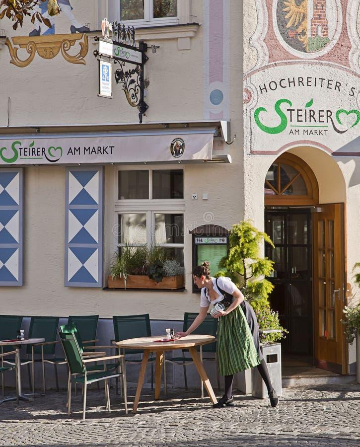 München, Deutschland - Kellnerin bereitet Tabellen in Freilicht restauran vor lizenzfreie stockfotografie