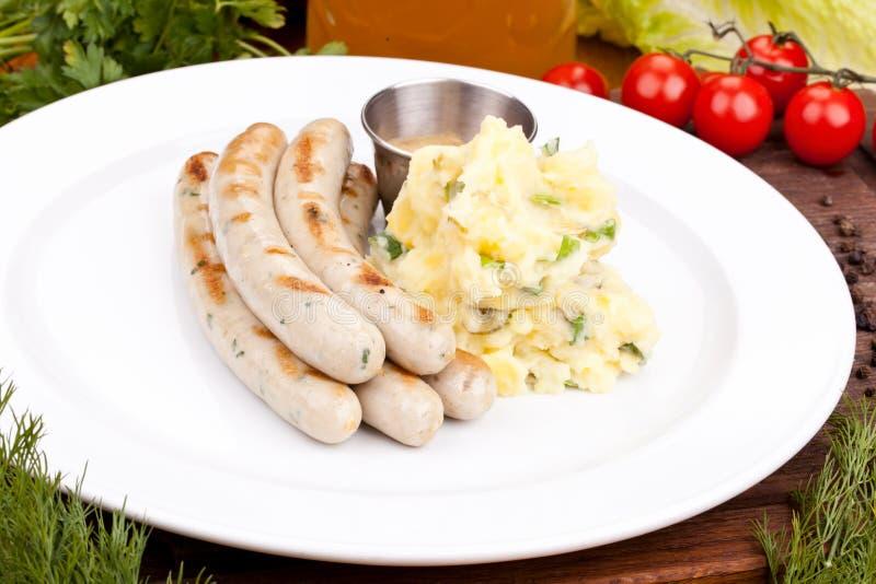 München-Würste mit Kartoffelsalat auf weißer Platte lizenzfreie stockfotos