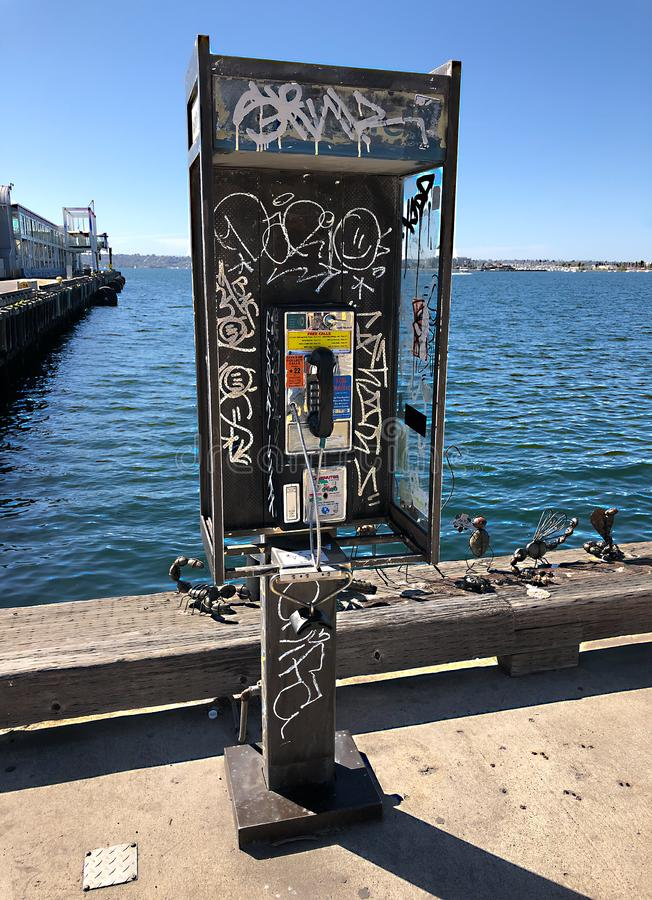 Münzbetriebene Telefonkabine mit Graffiti am Ozean lizenzfreie stockfotos