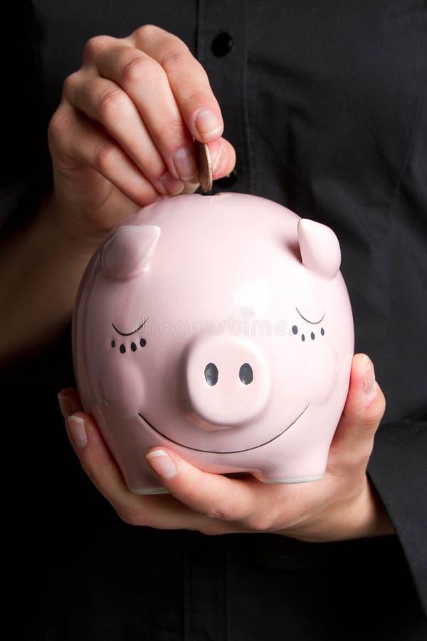 Münze in der Piggy Querneigung lizenzfreies stockfoto