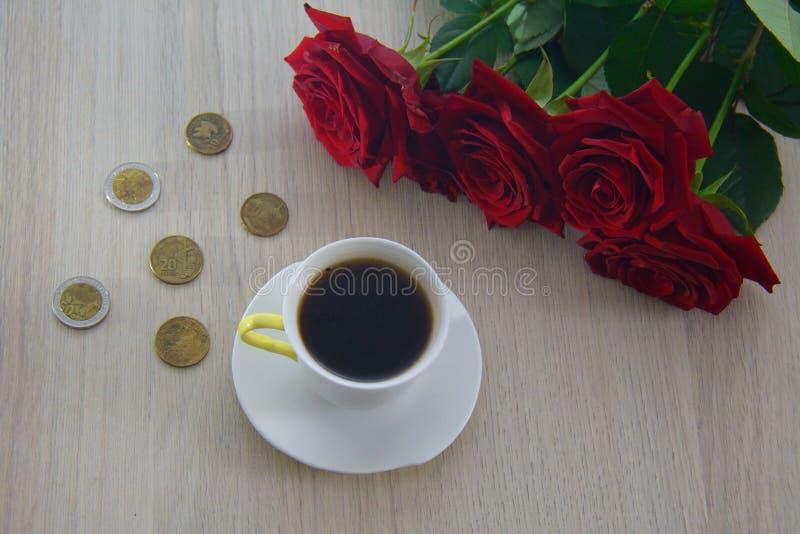Münzen auf dem Tisch zerstreut, mit Kaffee und Rosen lizenzfreie stockfotos