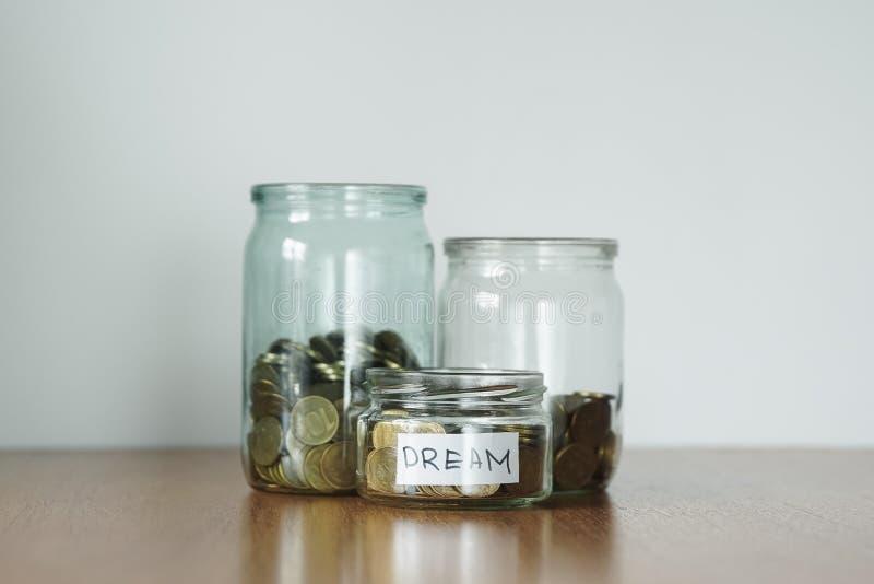 Münzen in den Glasgefäßen für unterschiedlichen Bedarf, Geldkästen Verteilung des Bargeldeinsparungenskonzeptes Autoaufkleber lizenzfreie stockfotos