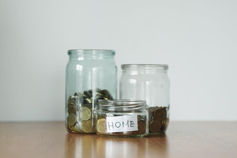 Münzen in den Glasgefäßen für unterschiedlichen Bedarf, Geldkästen Verteilung des Bargeldeinsparungenskonzeptes Hauptaufkleber stockfotos