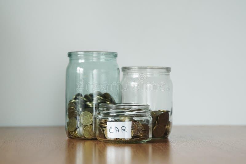 Münzen in den Glasgefäßen für unterschiedlichen Bedarf, Geldkästen Verteilung des Bargeldeinsparungenskonzeptes Traumaufkleber lizenzfreie stockfotografie