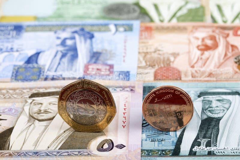 Münzen des jordanischen Dinars auf dem Hintergrund von Banknoten lizenzfreies stockbild