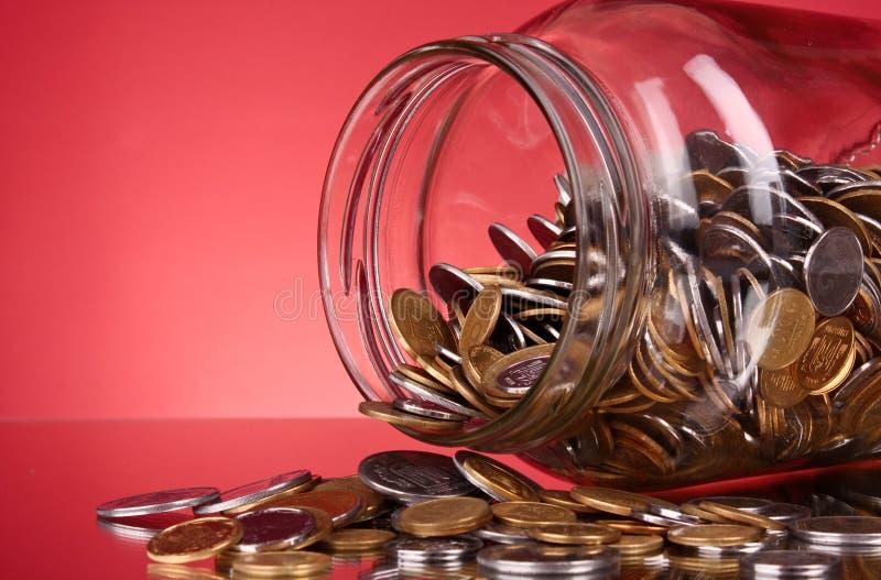 Münzen, die ein Geldglas überlaufen stockfotografie