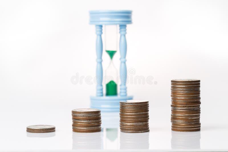 Münzen, die oben in der Diagrammform mit sandclock im backgroun stapeln stockbilder