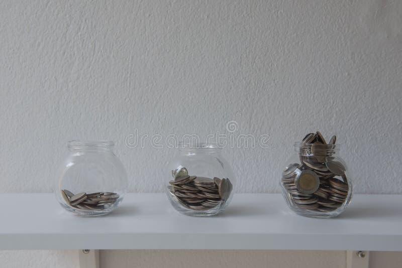 Münzen in einem Glasgefäß, Konzept Einsparungs-Geldschritt mit Ablagerungsmünze im wachsenden Geschäft des Bankstapels lizenzfreie stockfotos