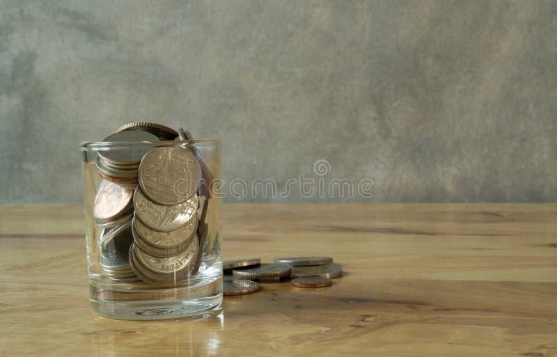 Münzen im Wasserglas lizenzfreie stockfotografie