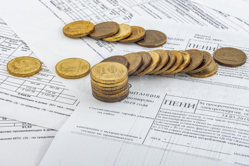 Münzen sind im Konto mit einer Strafe für Zahlung von Stromrechnungen stockbilder