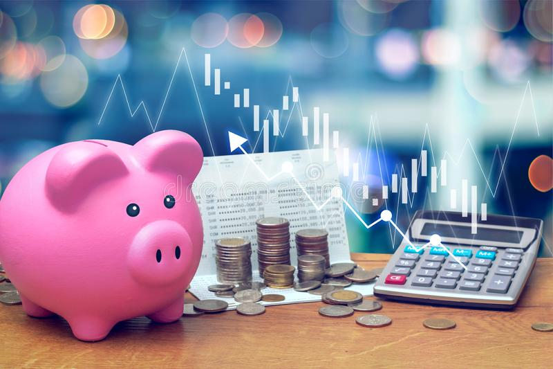 Münzen stapeln auf Sparkontobuch von der Bank mit rosa Sparschwein und Taschenrechner auf Holztisch mit Kerzenständer lizenzfreies stockfoto