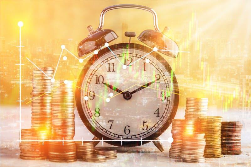 Münzen stapeln und Wecker auf goldenem Hintergrundgeschäft concep stockfotografie