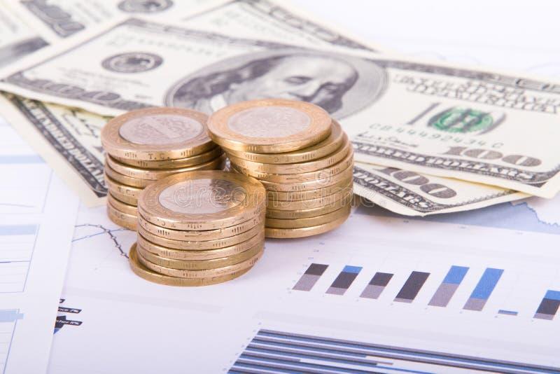 Münzen und Dollar-Banknoten auf Balkendiagramm-Grafiken stockfoto
