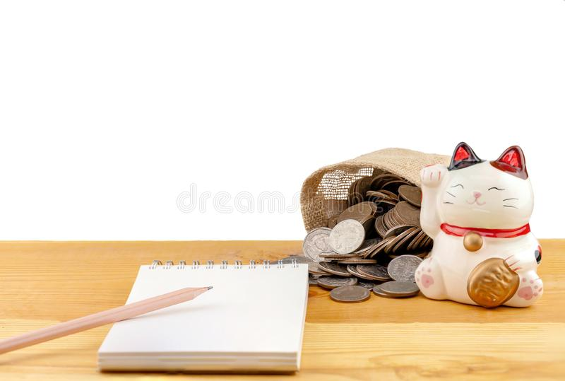 Münzen und glückliche Katze Japans auf hölzernem Tabellenhintergrund Schreibtisch mit Geldmünzen lizenzfreies stockbild