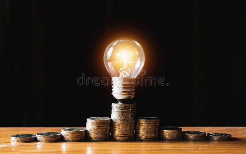 Münzen und Glühlampe gesetzt auf das hölzerne für Rettungsgeld, Energie c lizenzfreie stockfotos