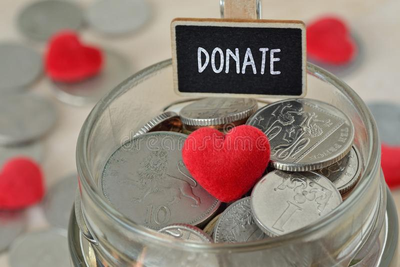Münzen und Herz im Glasgeldglas mit spenden Aufkleber - Nächstenliebekonzept stockbilder