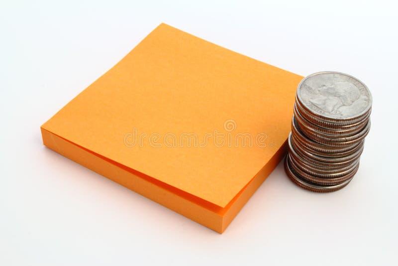 Münzen und orange Anmerkungsauflage lizenzfreie stockfotografie