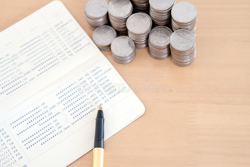 Münzen und Stift auf Sparkontosparbuch lizenzfreie stockfotografie