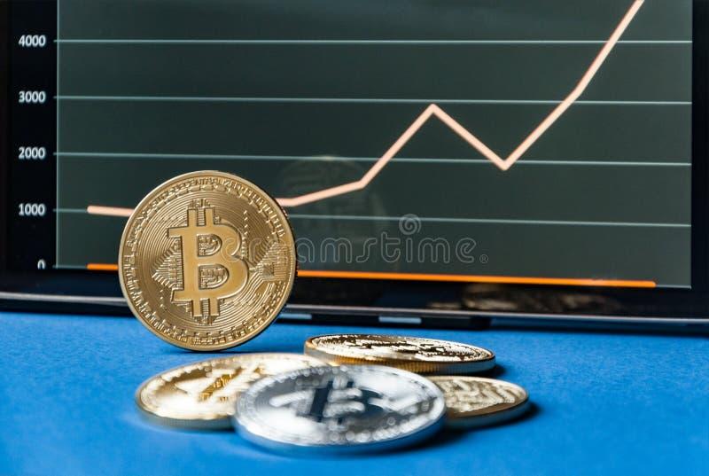 Münzen von bitcoins liegen auf dem Tisch vor und nahe bei der Tablette, auf der Diagramme von Bitcoin& x27; s-Kostenwachstum ist  stockbilder