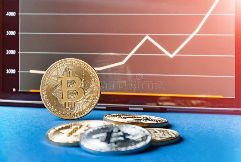 Münzen von bitcoins liegen auf dem Tisch vor und nahe bei der Tablette, auf der Diagramme von Bitcoin& x27; s-Kostenwachstum ist  lizenzfreie stockfotografie