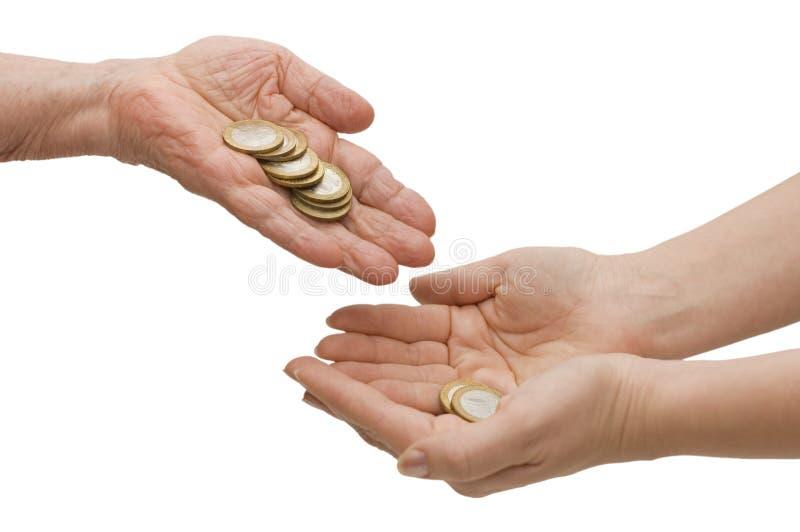 Münzen von den alten Händen in den Jungen lizenzfreie stockbilder